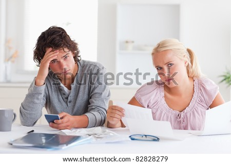 Despaired couple there accounts their living room - stock photo