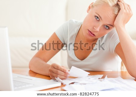 Despaired woman accounting looking into the camera in the living room - stock photo
