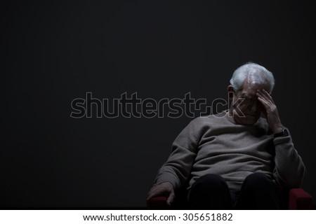 Despairing senior man on a dark background - stock photo