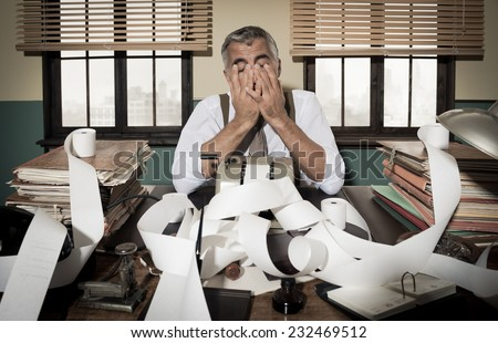 Desperate accountant head in hands surrounded by bills on paper tape, 1950s style office. - stock photo