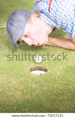 Desperate And Frantic Golfer Attempting To Inch His Green Ball Closer To The Golfing Hole By Blowing On It In A Humorous And Funny Golf Cheating Concept