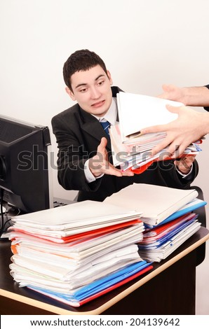 Desperate business man receiving a lot of paper work. Unhappy worker with a big pile of files to work on. - stock photo