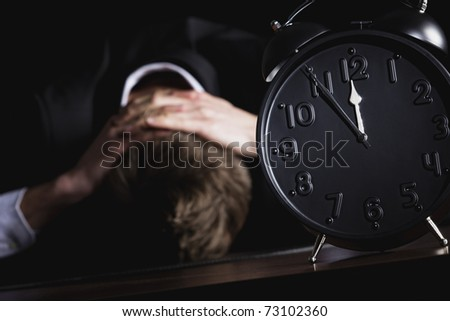 Desperate business person in dark suit sitting at office desk with head down being in despair with close up of alarm clock in foreground showing five minutes to twelve, isolated on black background. - stock photo