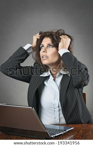 Desperate business woman in front of a laptop with hands in hairs
