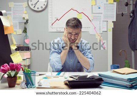 Desperate businessman at desk with negative business chart on background. - stock photo
