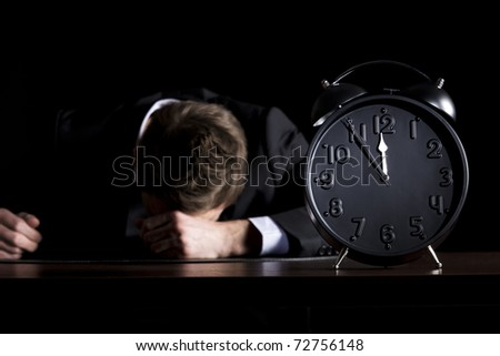 Desperate businessman in dark suit sitting at office desk with head down being in despair with close up of clock showing five minutes to twelve o-c'clock, low-key style isolated on black background. - stock photo
