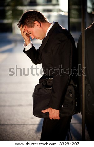 Desperate businessman leaning on an office building - stock photo