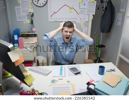 Desperate businessman screaming with head in hands and negative business chart on background.