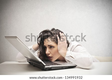 desperate businesswoman with hands in her hair fixed laptop - stock photo