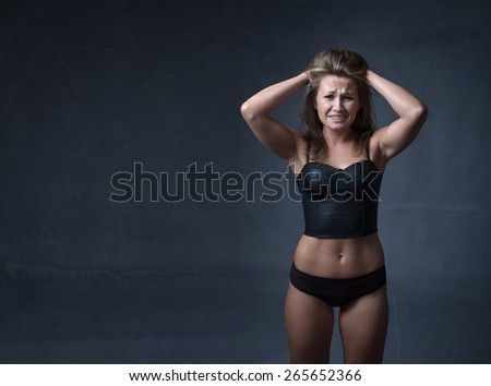 desperate girl with hands on hair, dark background and lingerie outfit - stock photo