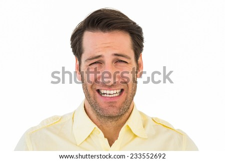 Desperate handsome man frowning at camera on white background - stock photo