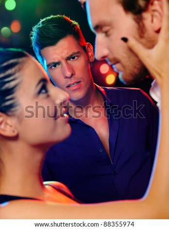 Desperate jealous man looking at flirting couple in discotheque.? - stock photo