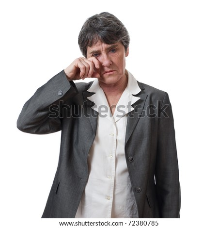 desperate mature businesswoman wiping tears isolated on white background - stock photo