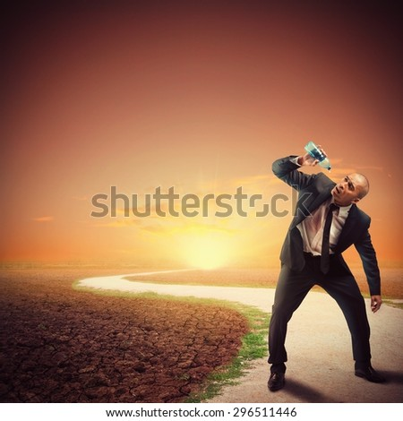 Desperate thirsty businessman in a dry path - stock photo