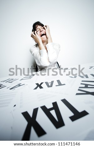 Desperate woman at her taxes-paperwork covered desk to crying bitter tears with her hands on face