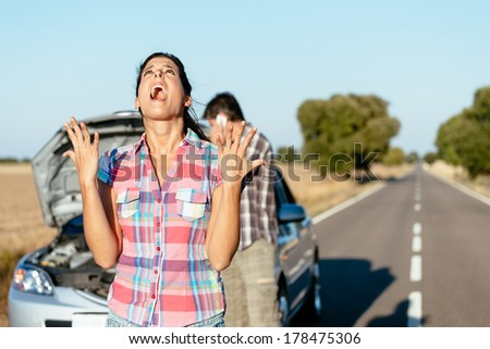 Desperate woman praying desperately because of car problems. Despair couple waiting for help after engine breakdown. - stock photo