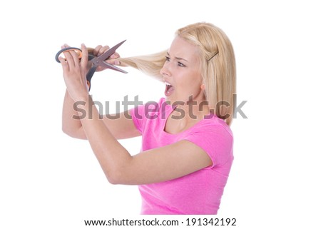 Desperate woman will cut her damaged blond hair. Isolated over white. - stock photo