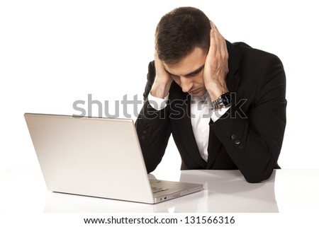 desperate young businessman leaning on both hands behind his laptop - stock photo