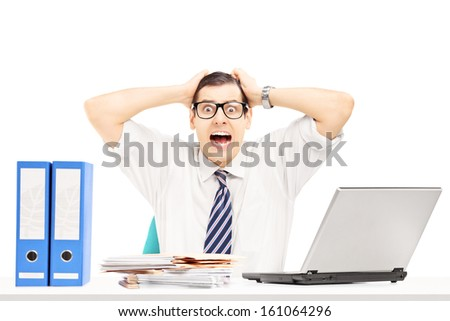 Desperate young businessman shouting in his office isolated on white background