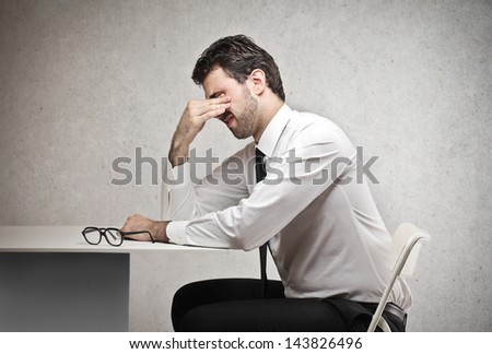desperate young businessman sitting in his office - stock photo