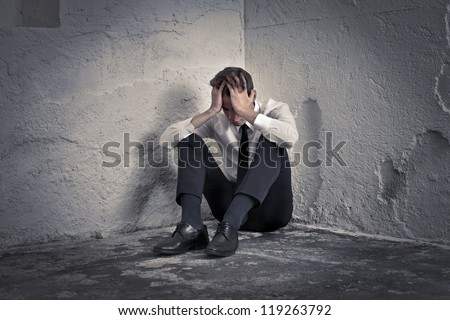 Desperate young man in tie in the corner of a basement - stock photo