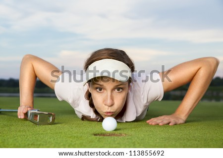 Desperate young woman golf player with putter in hand lying on green and blowing golf ball into cup, close up.