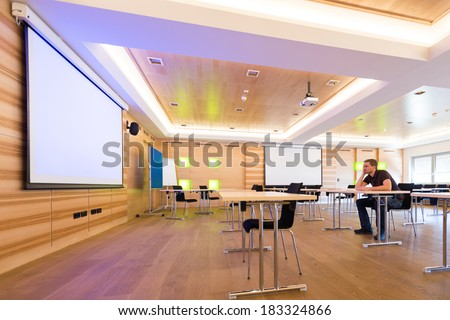 desperated man in conference room with white projection screen  - stock photo