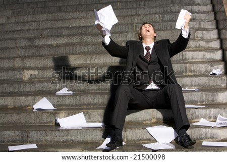 Desperated professional raising his arms upwards and crying during recession - stock photo