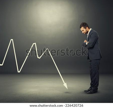 despondent businessman looking at negative graph over dark background - stock photo