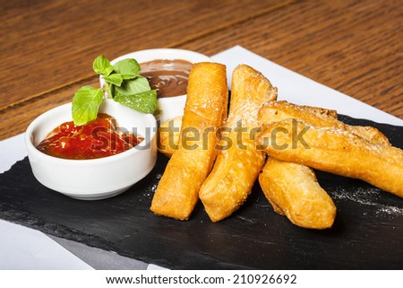 Dessert - fritters with confiture and chocolate cream on restaurant table - stock photo