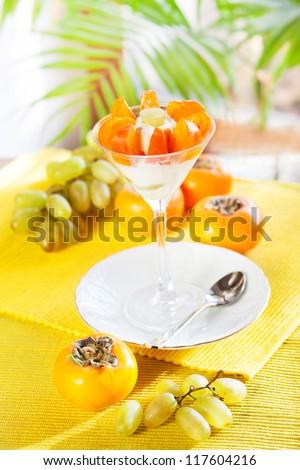 Dessert grapes, persimmons, cream - stock photo