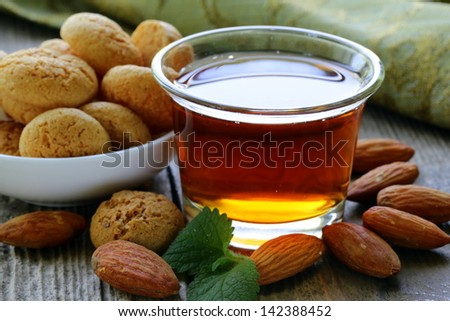 Dessert liqueur Amaretto with almond biscuits (amarittini) and nuts - stock photo