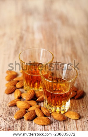 Dessert liqueur Amaretto with almond nuts, on wooden table - stock photo