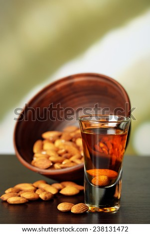Dessert liqueur Amaretto with almond nuts, on wooden table, on light background - stock photo