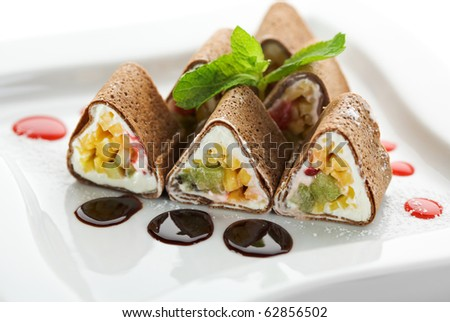Dessert Maki Sushi - Chocolate Roll with Various Fruit and Cream Cheese inside. Chocolate Pancake outside. Served with Chocolate Sauce - stock photo