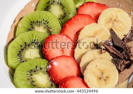 Dessert of kiwi, strawberry, banana and chocolate - stock photo
