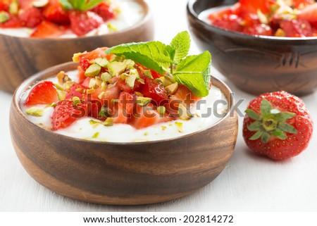 dessert of yogurt with fresh strawberries, pistachios and mint, close-up, horizontal - stock photo