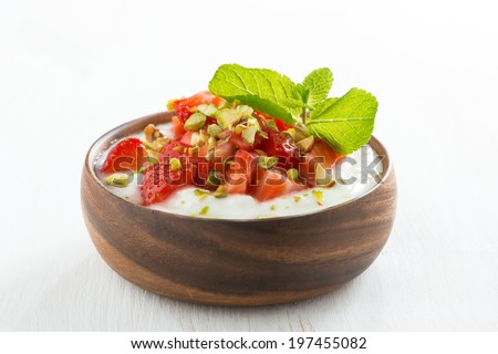 dessert of yogurt with fresh strawberries, pistachios and mint in wooden bowl, close-up - stock photo