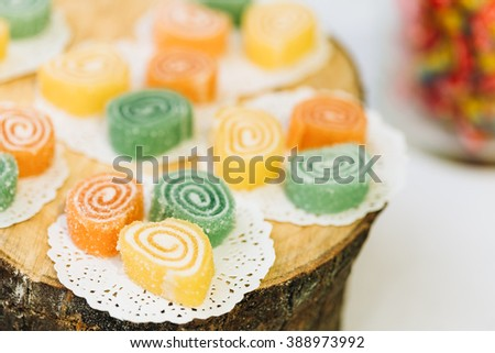 Dessert Sweet Tasty Yummy Colorful Jellies in Candy Bar On Table. Delicious buffet on wooden stump. - stock photo