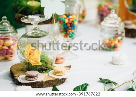 Dessert Sweet Tasty Yummy Colorful macarons in Candy Bar On Table. Delicious buffet on wooden stump. - stock photo