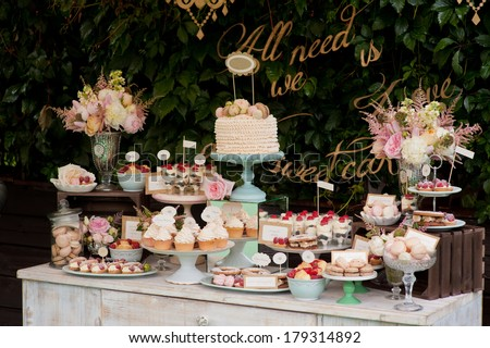 Dessert table for a party. Ombre cake, cupcakes, sweetness and flowers