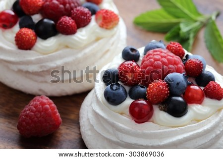Dessert with berries on a meringue with cream. - stock photo