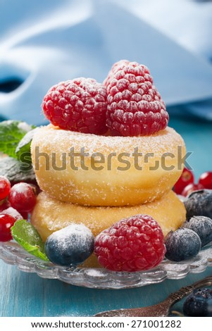 Dessert with mini donuts and berries on plate under powdered sugar on blue wooden background.  Tasty donuts closeup. Doughnut. Selective focus.  - stock photo