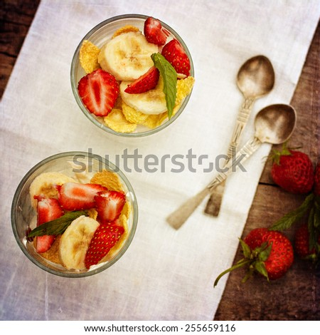 Dessert with strawberries.Cheese, strawberry, banana, cornflakes on the table. Breakfast. Toned photo. - stock photo