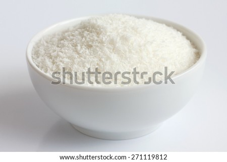 Dessicated coconut in white ceramic bowl. - stock photo