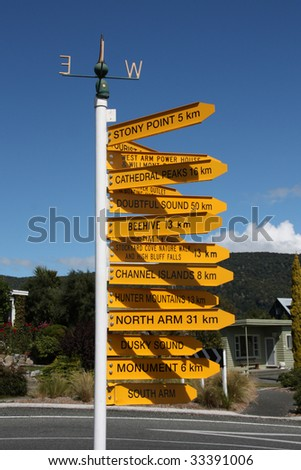 Destinations in New Zealand - variety of direction signs in Manapouri - stock photo
