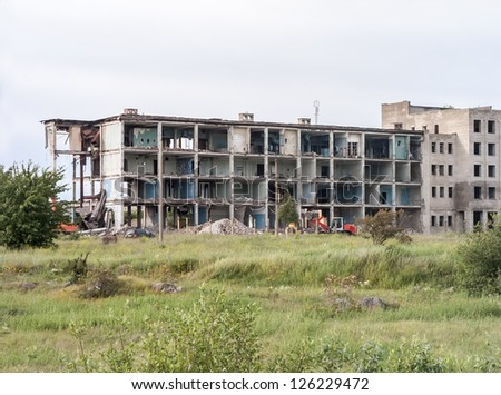 Destroyed building in industrial style with pile of debris - stock photo
