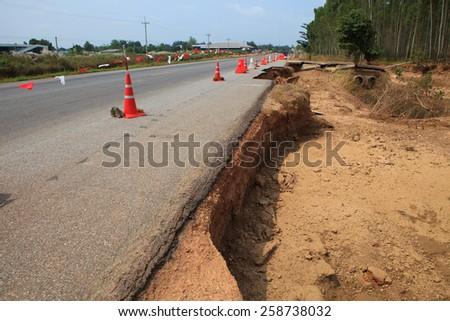 destruction of asphalt highways road after hard rain storm and flood water past - stock photo