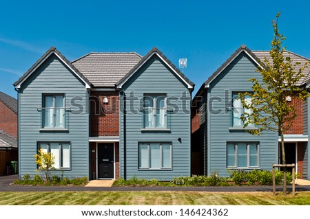 detached british residential house (beach style) with small entrance garden (blue sky) - stock photo