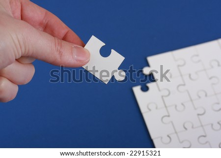 Detached corner of plain white jigsaw puzzle being held in someones hand with the jigsaw puzzle out of focus on a blue background